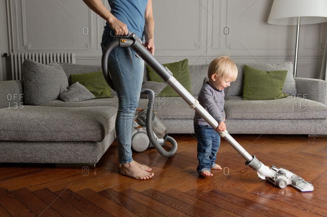 Happy toddler helping mother vacuum hardwood floor in living room