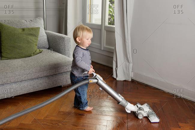 Cute baby using vacuum on hardwood floor in living room