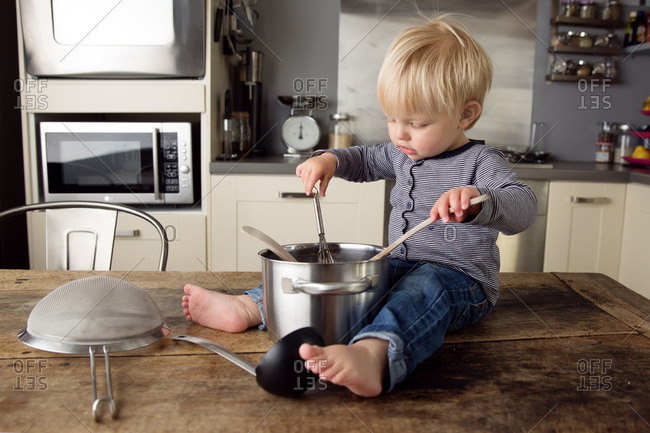 Cute toddler sitting on kitchen table playing with utensils