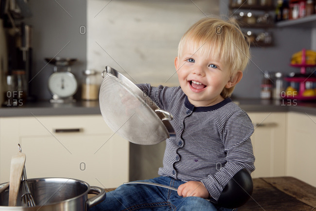 Happy toddler sitting on kitchen table playing with utensils