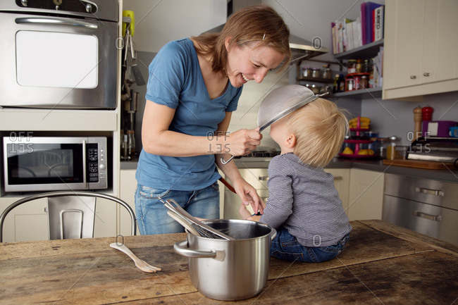 Happy mother and baby playing with utensils in kitchen