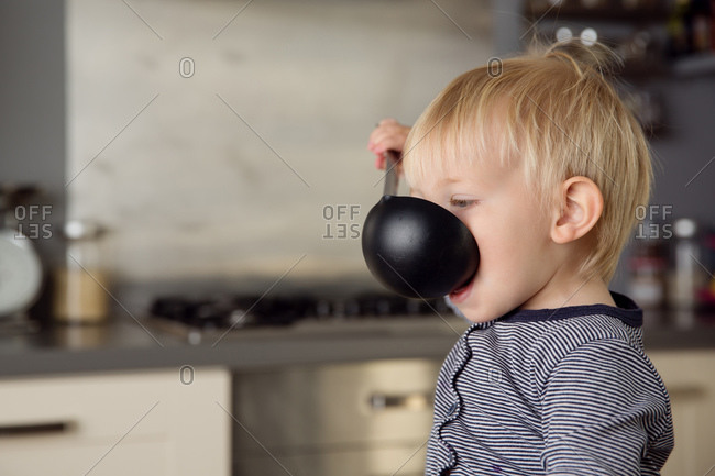 Cute toddler in kitchen drinking from ladle