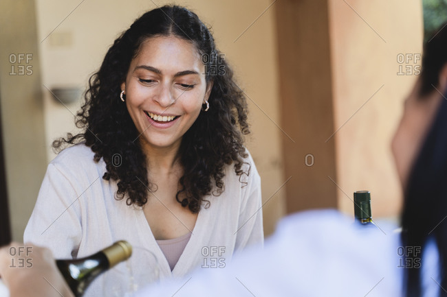Friend pouring champagne into woman's glass while sitting in backyard