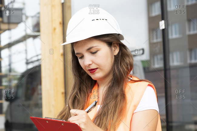 Construction worker making notes on clipboard