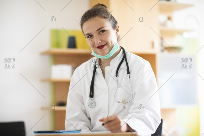 Female doctor taking notes and smiling