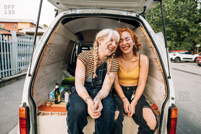 Female couple laughing, sitting in back of van