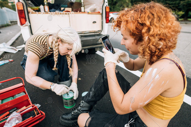 Woman photographing her girlfriend painting