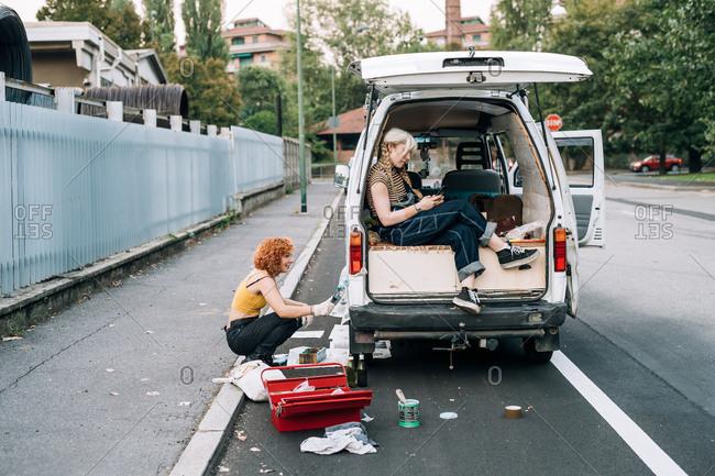 Young women working on van