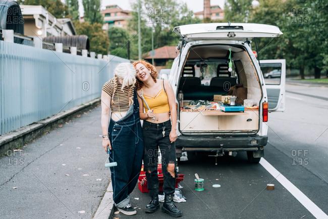 Happy female couple, standing near their van