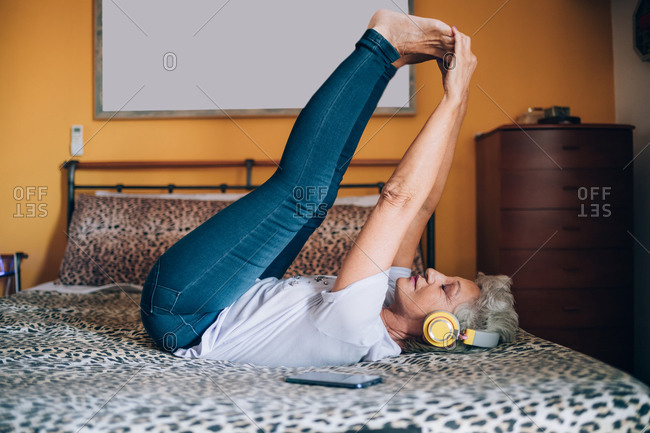 Woman stretching on bed, listening to headphones