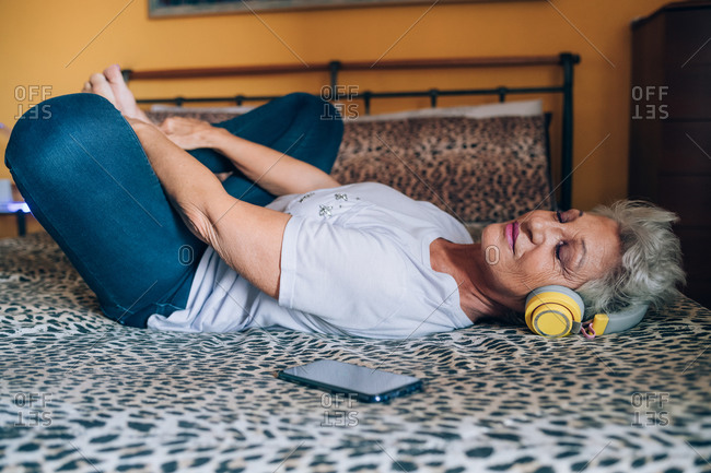 Senior woman relaxing on bed, listening to headphones