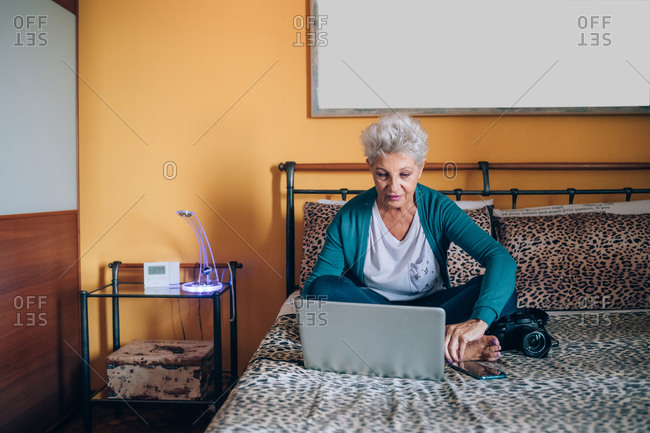 Photographer sitting on bed with laptop