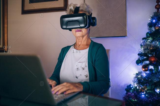Woman using virtual reality headset and laptop
