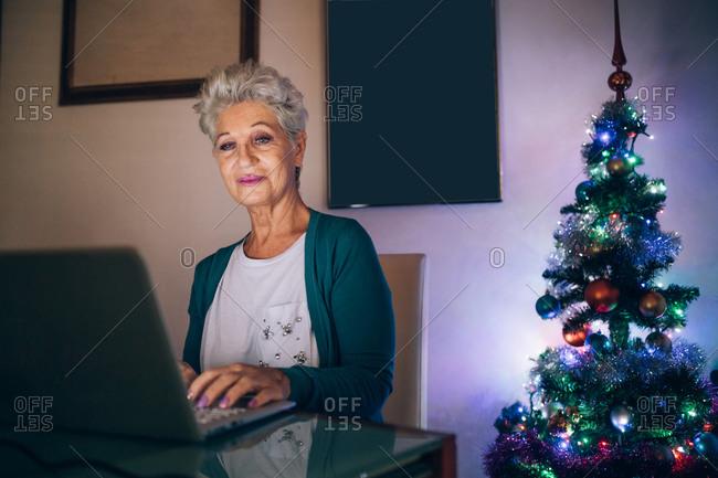 Woman Christmas shopping online, next to Christmas tree