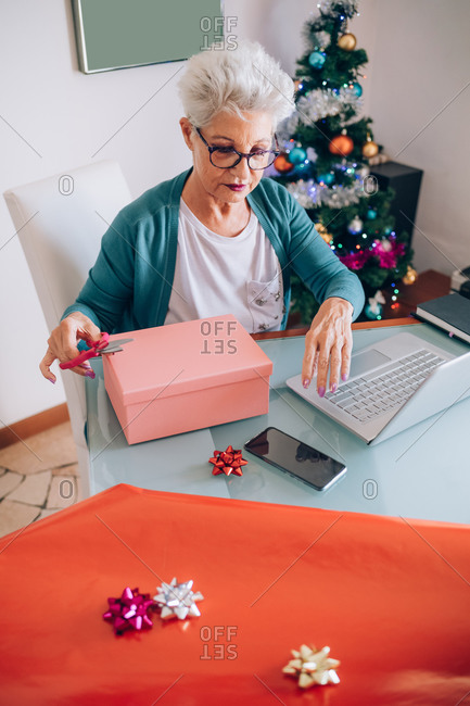Woman wrapping Christmas presents, looking at her phone