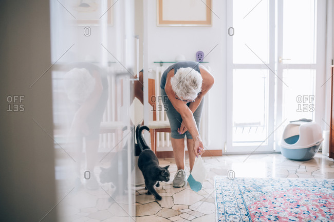 Senior woman at home with pet cat