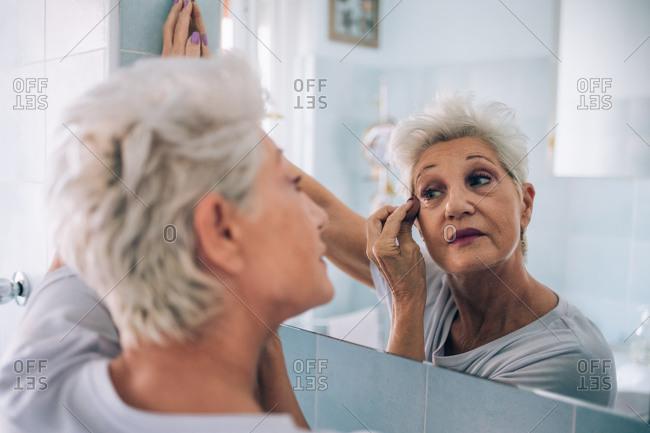Senior woman looking in mirror, applying makeup