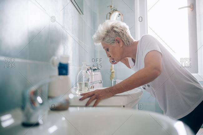 Woman brushing her teeth in bathroom