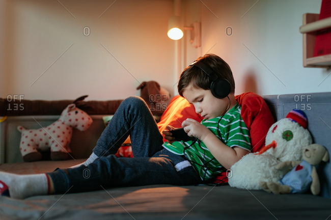 Young Boy Wearing Headphones Resting on Bed Surrounded by Soft Toys Playing Games on Smartphone.
