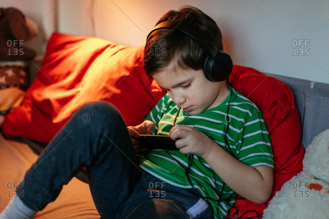 Young Boy with Headphones Relaxing on Bed Playing with Smartphone in His Room.