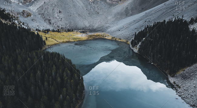 Aerial view of a lake next to a mountain and a forest. Reflection.