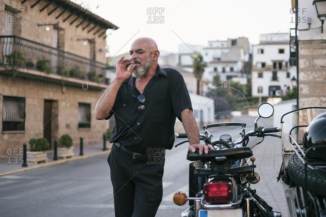 Smoking 55 years old man in rural city near to his sidecar. Jaen, Spain