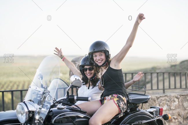Pretty women on sidecar bike smiling and looking at camera