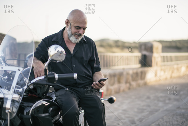 Senior man looking smartphone on sidecar bike. Jaen, Spain