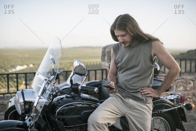 Blonde casual man on his sidecar bike parking, looking telephone hand having a break in his journey
