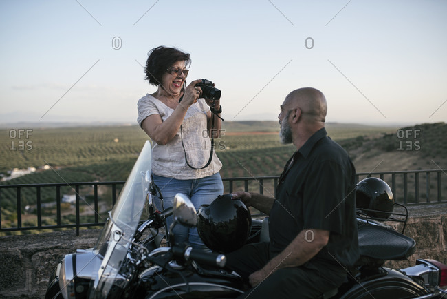 Senior couple having fun taking pictures and traveling with their sidecar bike