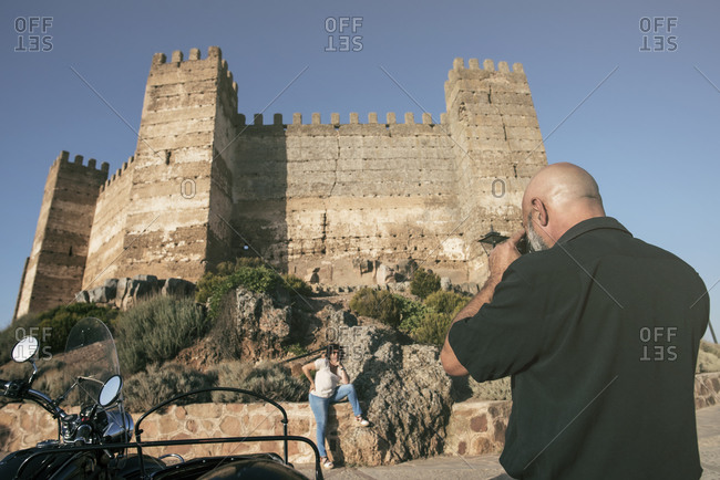 Banos de la Encina, Spain. Mature man taking picture of her wife posing near to the castle in romantic travel.