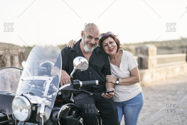 Senior couple on sidecar bike posing for portrait while looking smartphone, Jaen, Spain