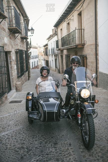 Senior couple traveling on sidecar bike in rural scene