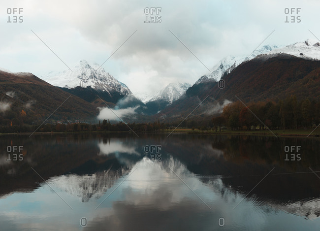 Snow capped mountains reflected on a calm lake in French Pyrenees during autumn