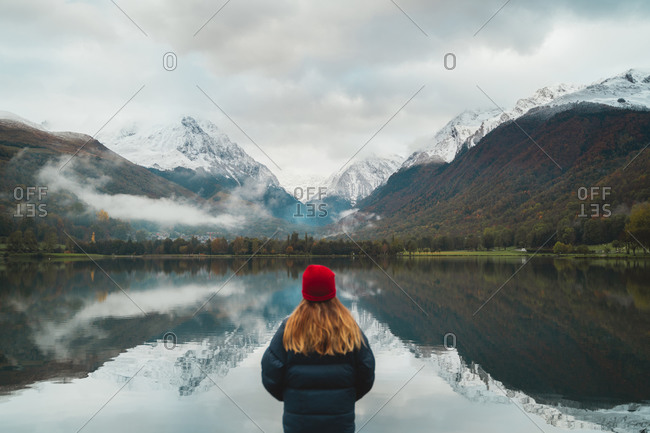Blonde girl wearing a red wool hat standing in front of a calm lake with snow capped mountains in background in French Pyrenees