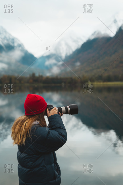 Blonde caucasian girl taking photos with a big camera on the shore of a beautiful lake in Loudenvielle, France