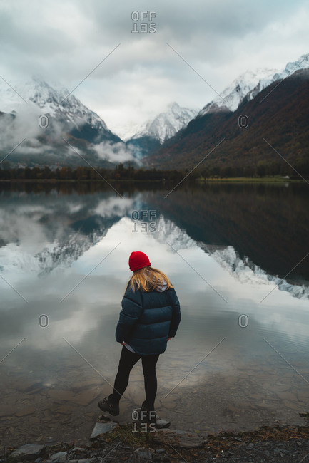 Blonde girl wearing mountaineering clothes stepping into a calm water lake in French Pyrenees