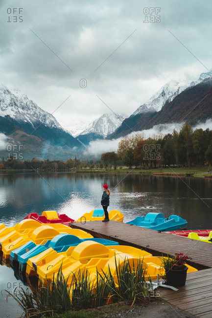 Blonde girl standing on the pier of a lake in Pyrenees on a cloudy day