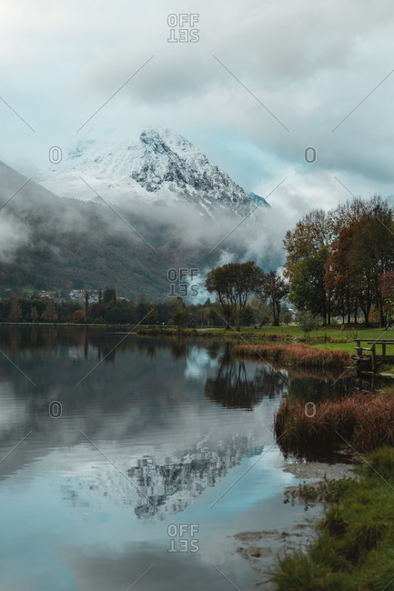 Gorgeous view of a snowy mountain reflected on a calm lake with autumnal trees on the shore