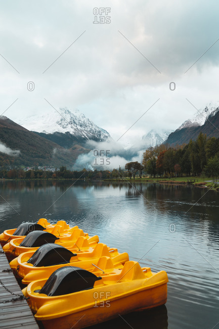 Yellow boats tied to the pier of a lake in Loudenvielle, Hautes Pyrenees during autumn