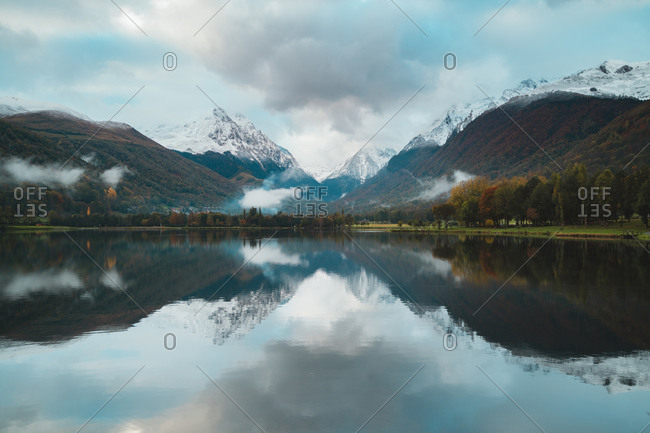 Panoramic view of a calm Loundenvielle Lake during a beautiful cloudy day during autumn