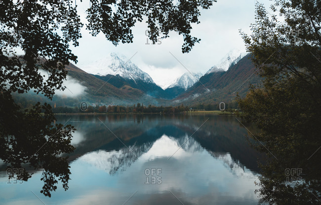 Genos Lake framed by leaves during a moody day in Hautes Pyrenees