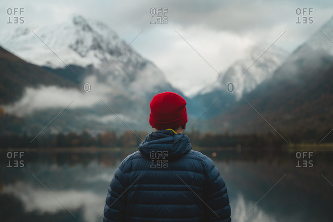 Young hiker wearing red wool beanie and blue down jacket standing in front of a beautiful lake in snowy Pyrenean mountains