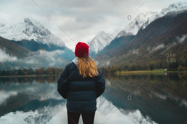 Back shot of female hiker standing in front of a big lake with her hands inside the pockets of down jacket