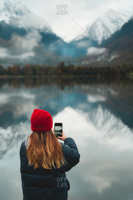 Blonde caucasian girl wearing a red wool beanie taking a photo of the beautiful lake on her smart phone