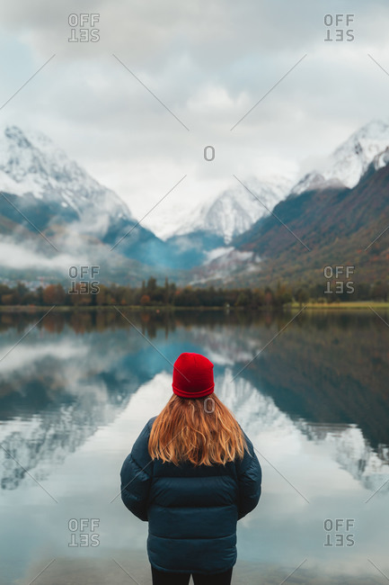Blonde caucasian girl wearing red wool beanie staring at a beautiful calm lake in Pyrenees on a moody autumn day