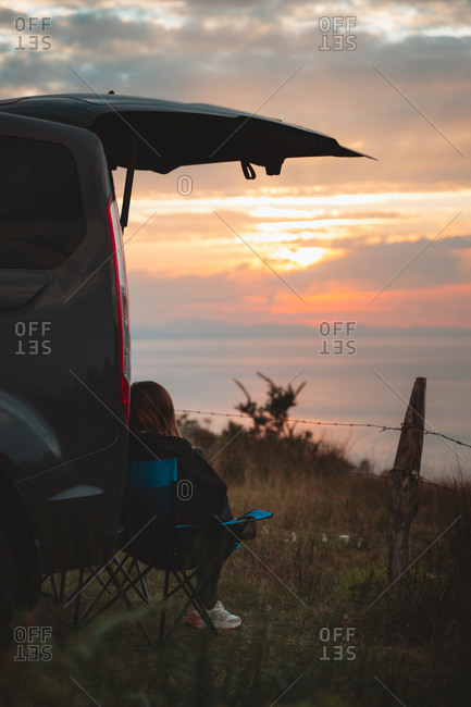 Young blonde girl sitting on a camping seat under the trunk of a van watching the sunset