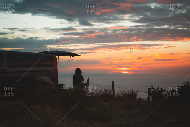 Lonely person standing on the side of a camper van watching the sunset