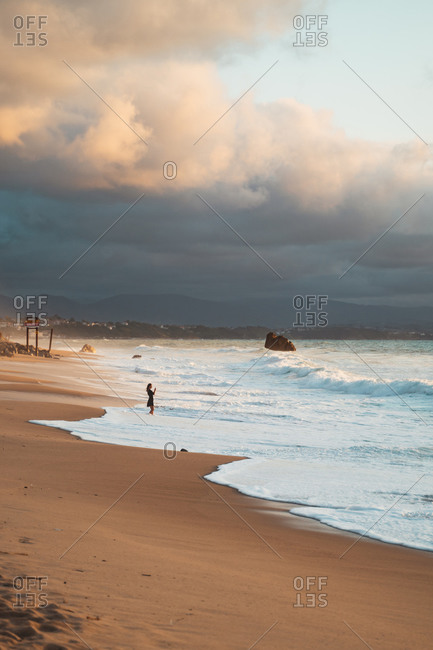 Young girl wearing a short black dress taking a photograph of the waves dipping her feet on the shore