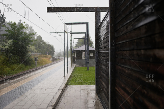 Wooden buildings and wet rails located on railroad station during downpour in countryside